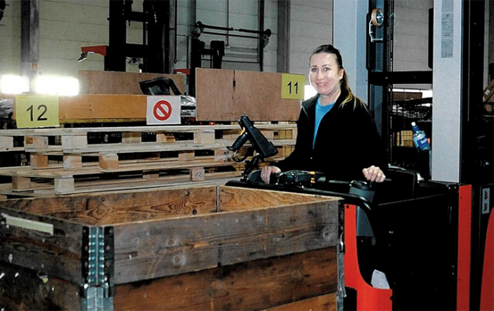 Warehouse Operator Jane Lindberg uses a laptop and scanner when picking goods from the shelves