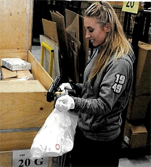 Warehouse Operator Jacqueline Forslund scans a product to be shipped to a dealer.
