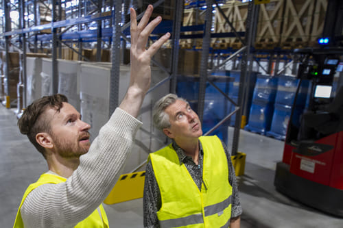 Two warehouse workers in yellow safety vest discussing