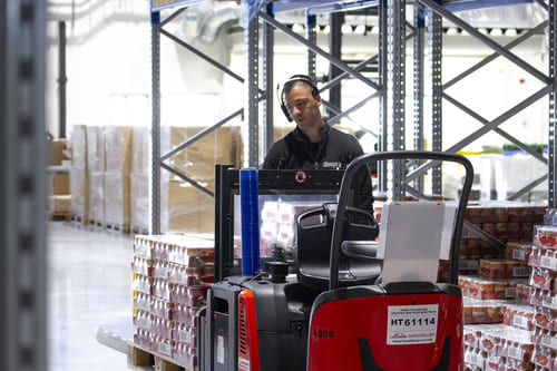 A warehouse worker driving a red forklift in a warehouse