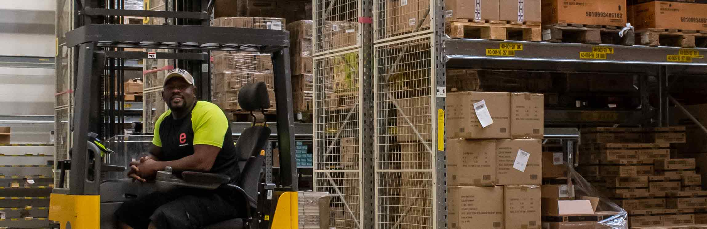 warehouse worker sitting on a truck in a warehouse