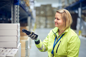 Woman wearing warning clothes in a warehouse, scanning package